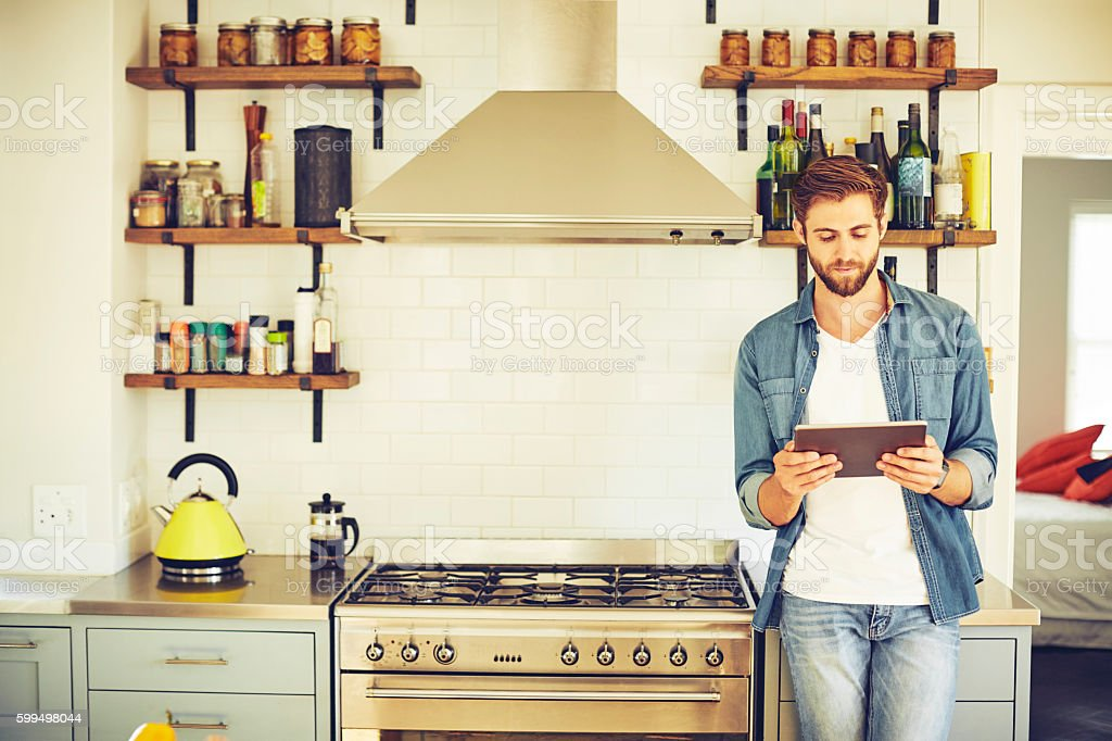 Handsome young man using tablet PC in kitchen stock photo