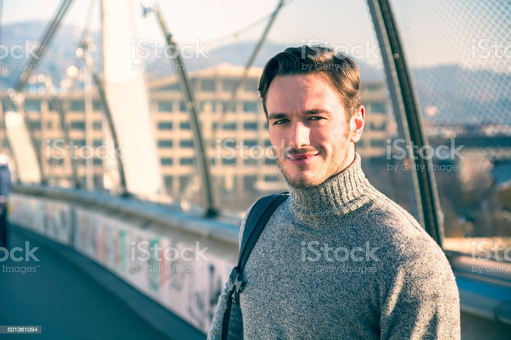 Handsome young man walking in city with backpack stock photo