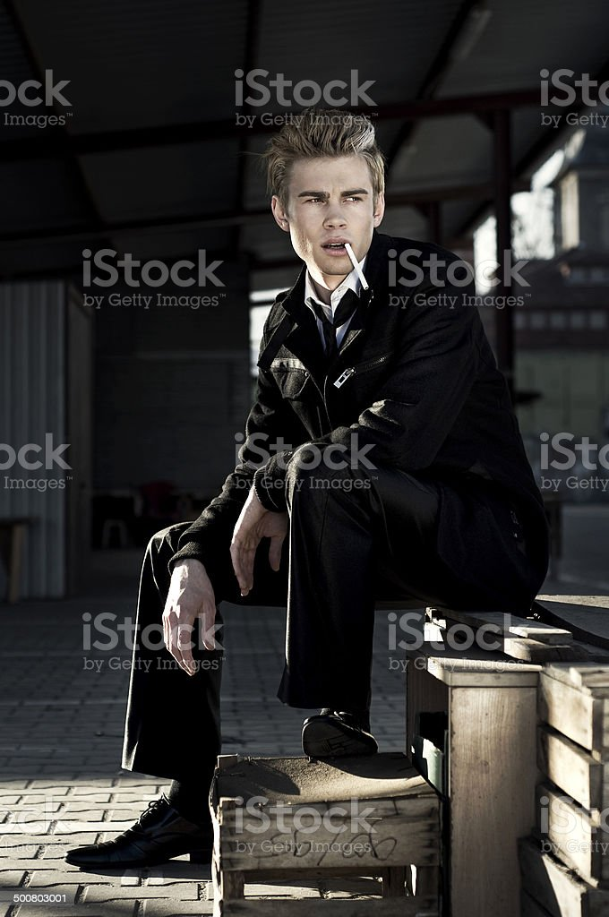 Handsome young man with a cigarette stock photo