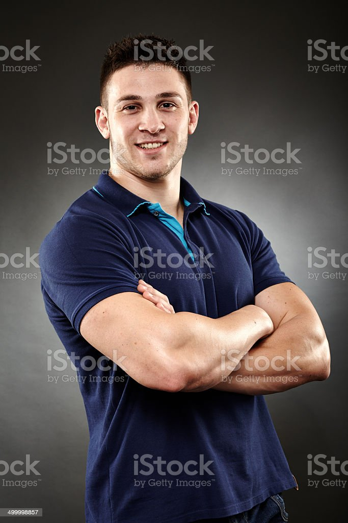 Handsome young man with arms folded stock photo