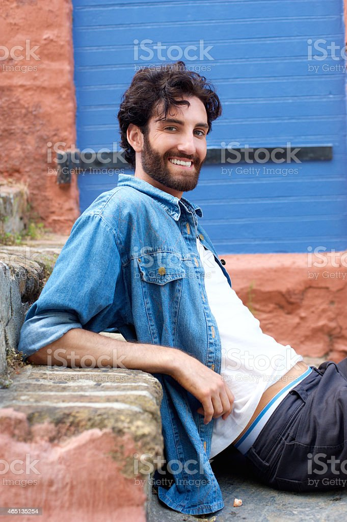Handsome young man with beard sitting on step stock photo