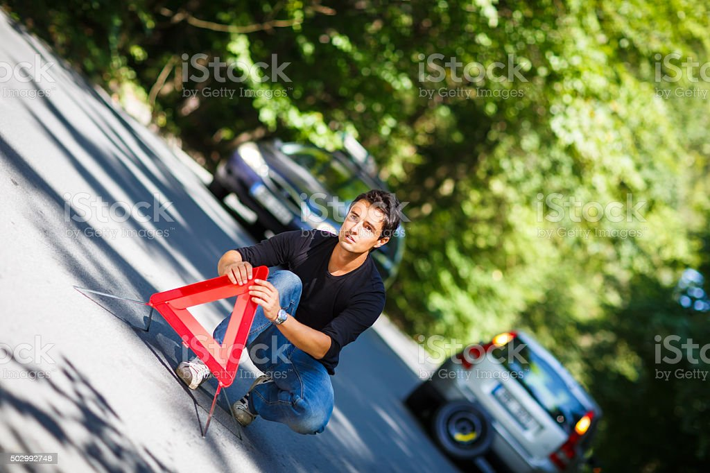 Handsome young man with his car broken down stock photo