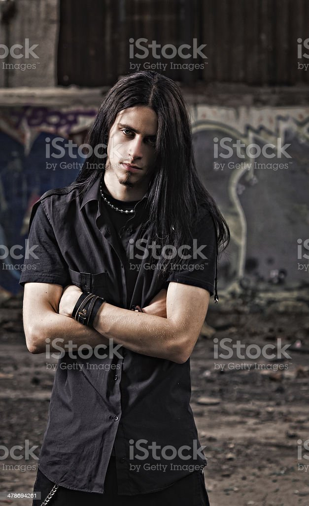 Handsome young man with long hair among industrial ruins stock photo