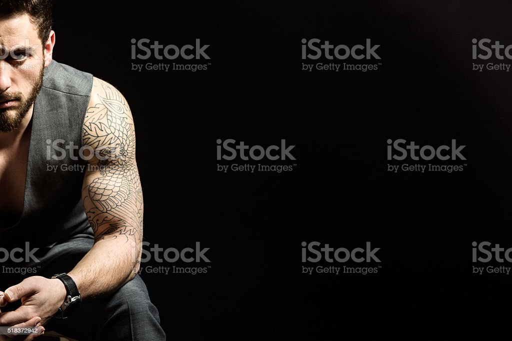 Handsome young man with tattoos posing. Isolated on black. stock photo