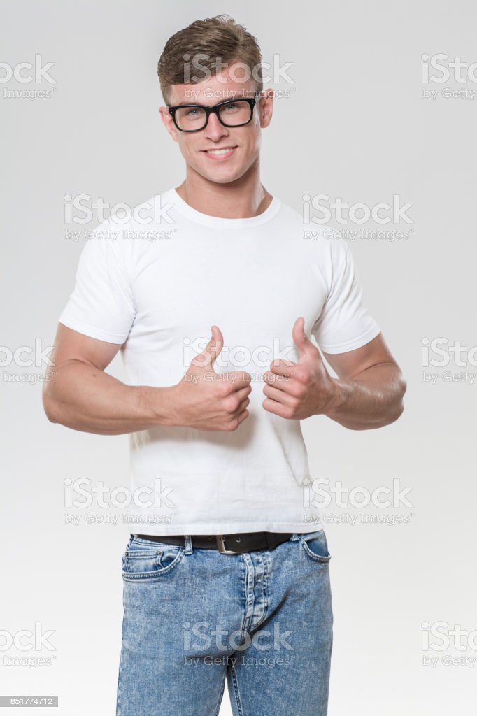 Handsome young man with thumbs up. Picture taken in a studio with grey background. stock photo