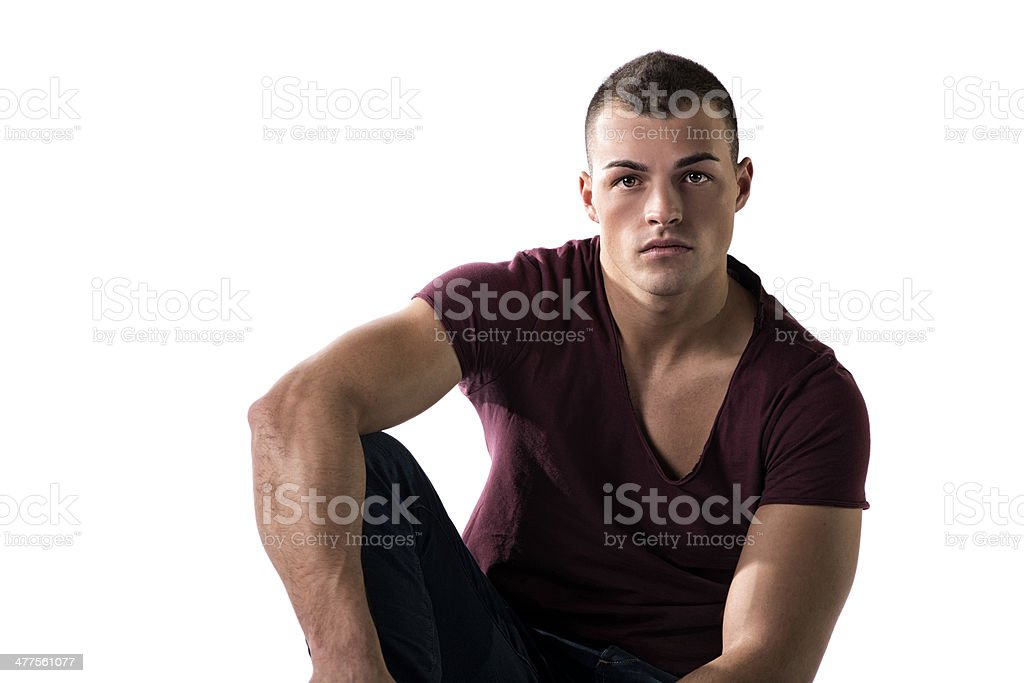 Handsome young man with t-shirt and jeans, sitting royalty-free stock photo
