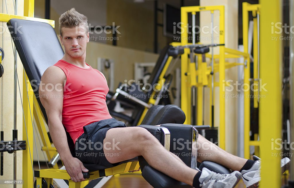 Handsome young man working out on gym equipment royalty-free stock photo
