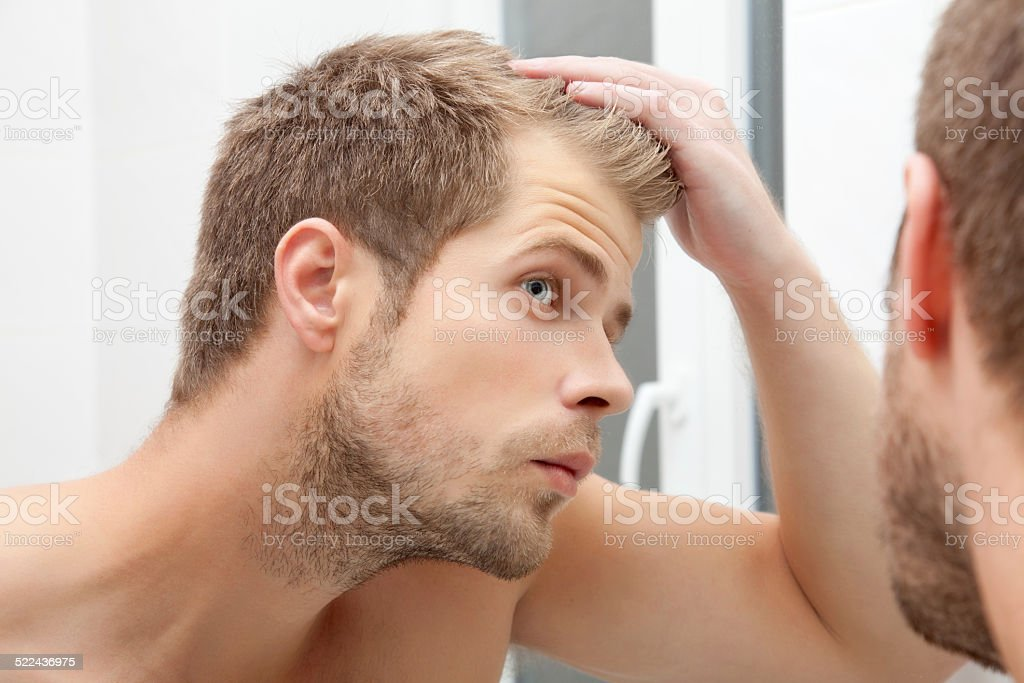 Handsome young man worried about hairloss stock photo