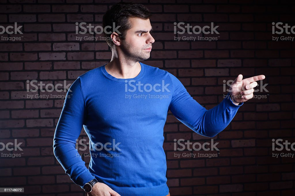 Handsome young manindicates the direction the finger stock photo