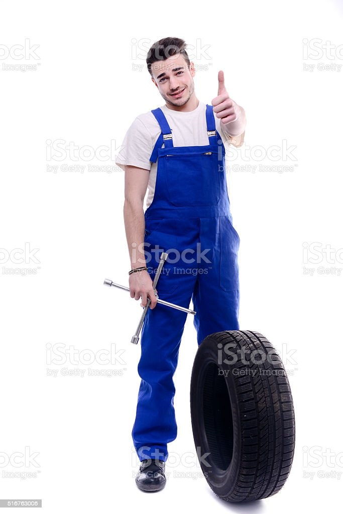 handsome young mechanic holding tire isolated on white background stock photo