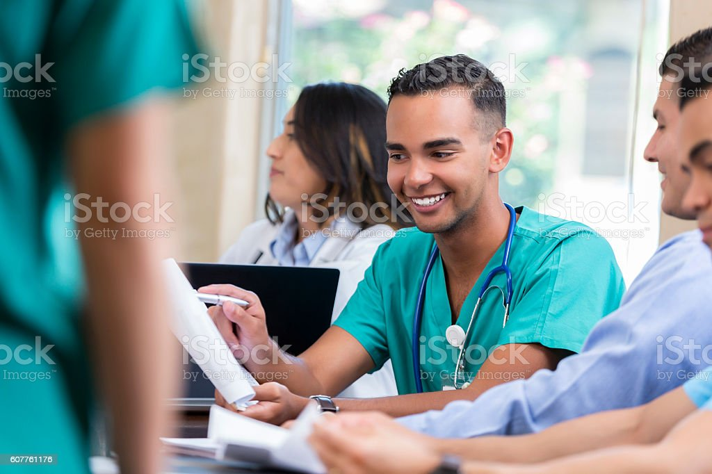 Handsome young medical professional talks during staff meeting stock photo