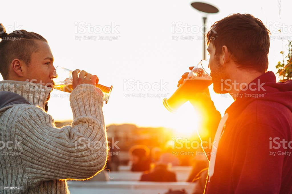handsome young men drinking beer in front of backlit stock photo
