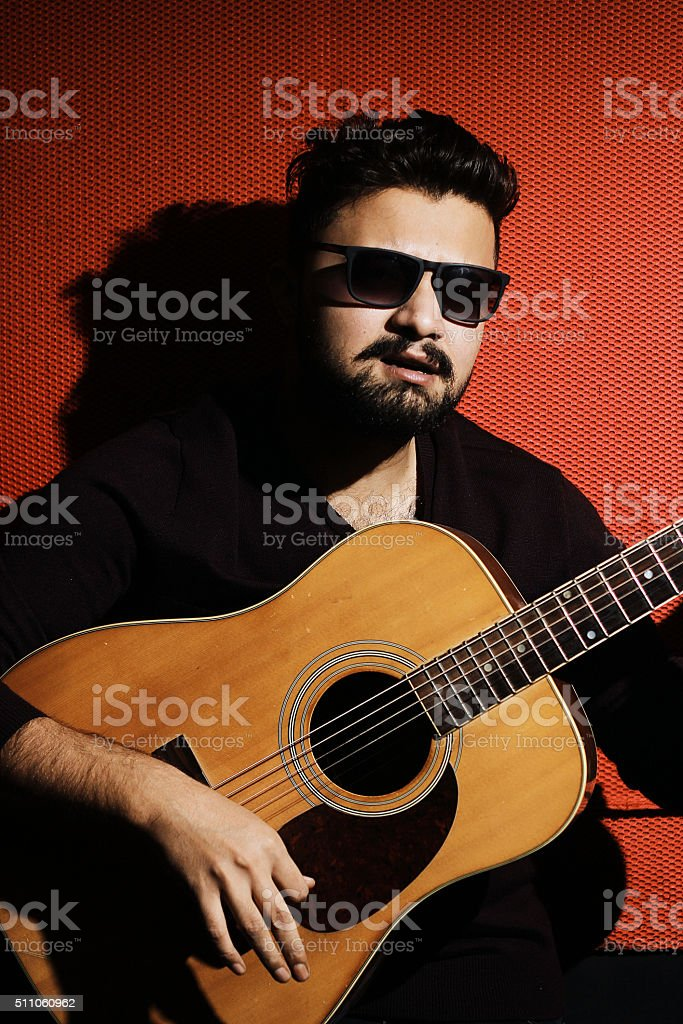 Handsome young musician playing the guitar and singing stock photo