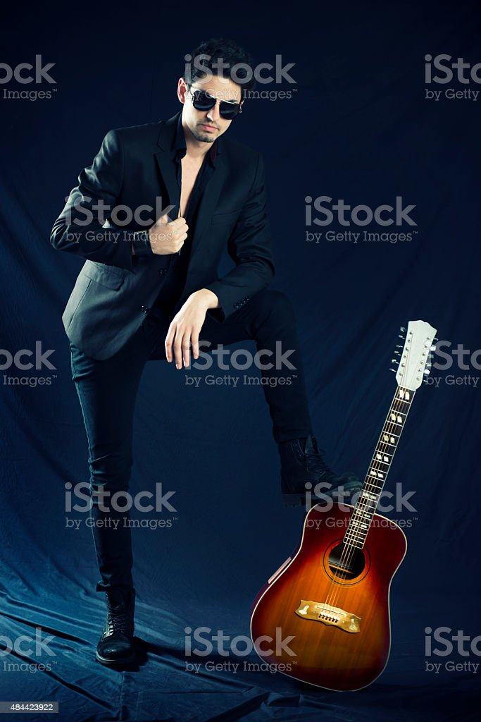Handsome Young Musician Posing with Acoustic Guitar stock photo