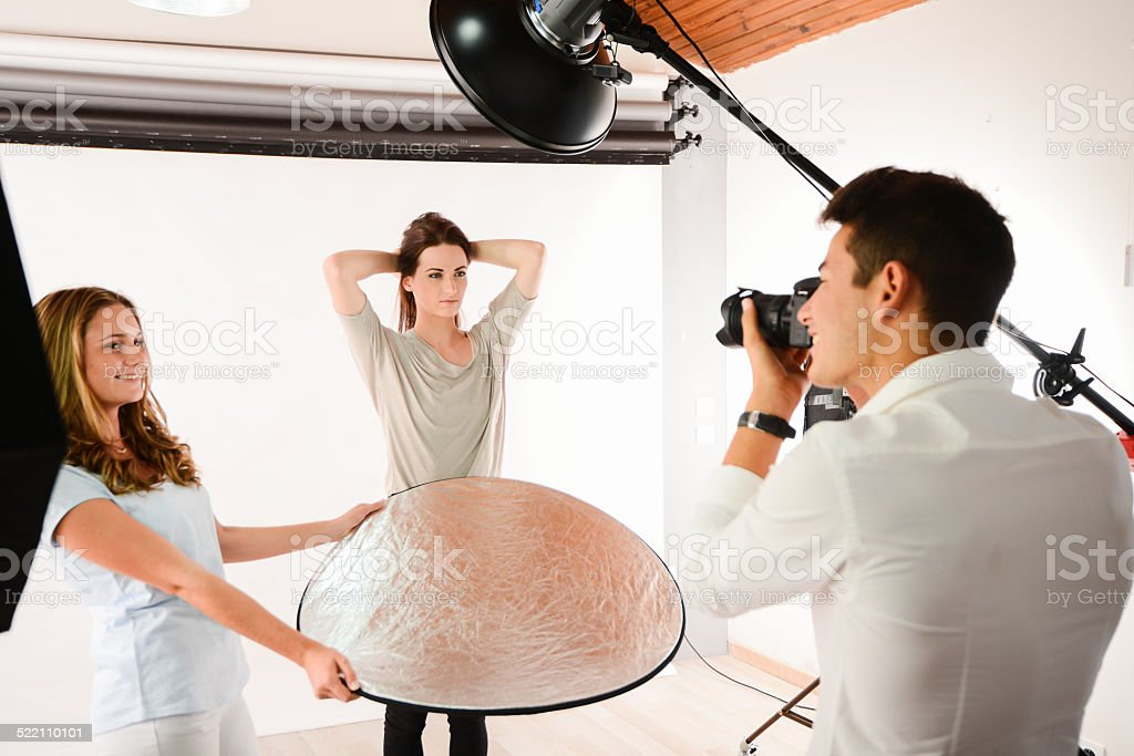 handsome young photographer taking pictures of beautiful girl  fashion model stock photo
