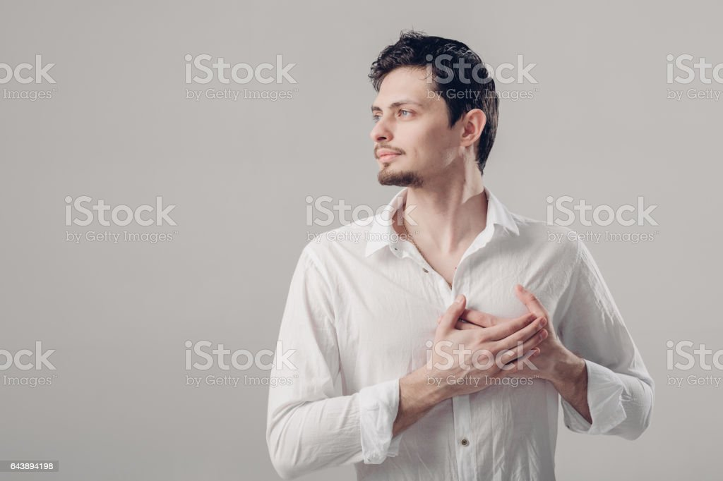 handsome young proud man in shirt holding hand on chest on grey stock photo