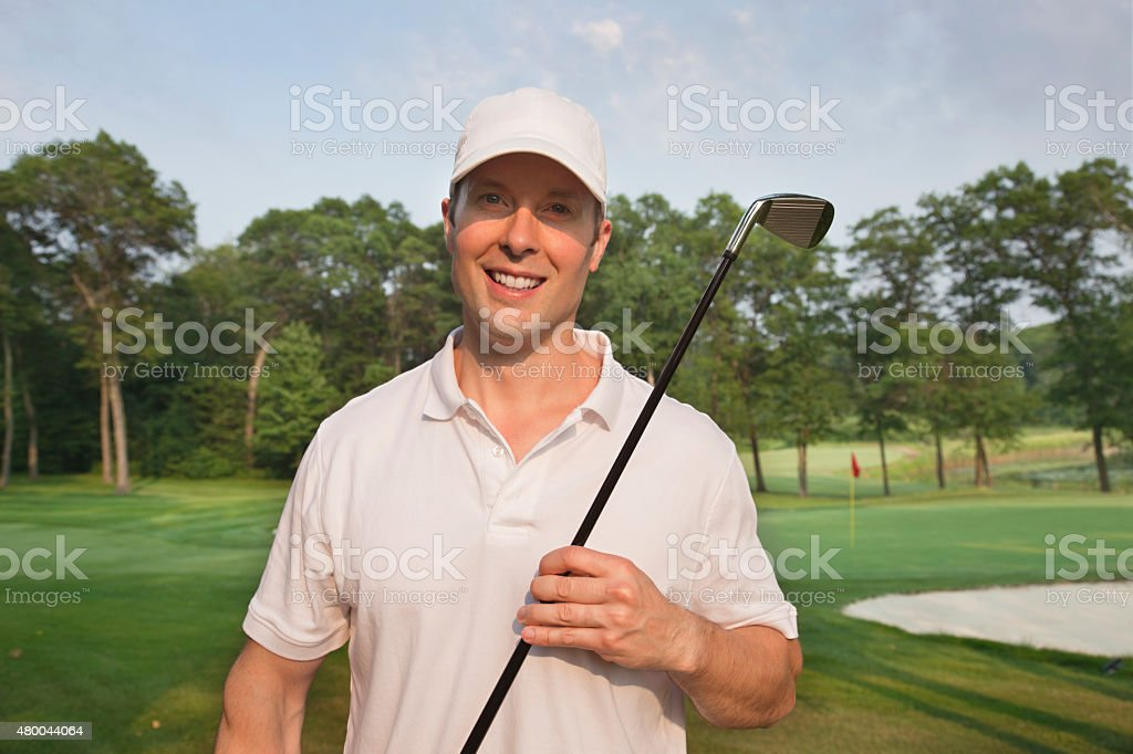 Handsome young smiling golfer holds club on a course stock photo