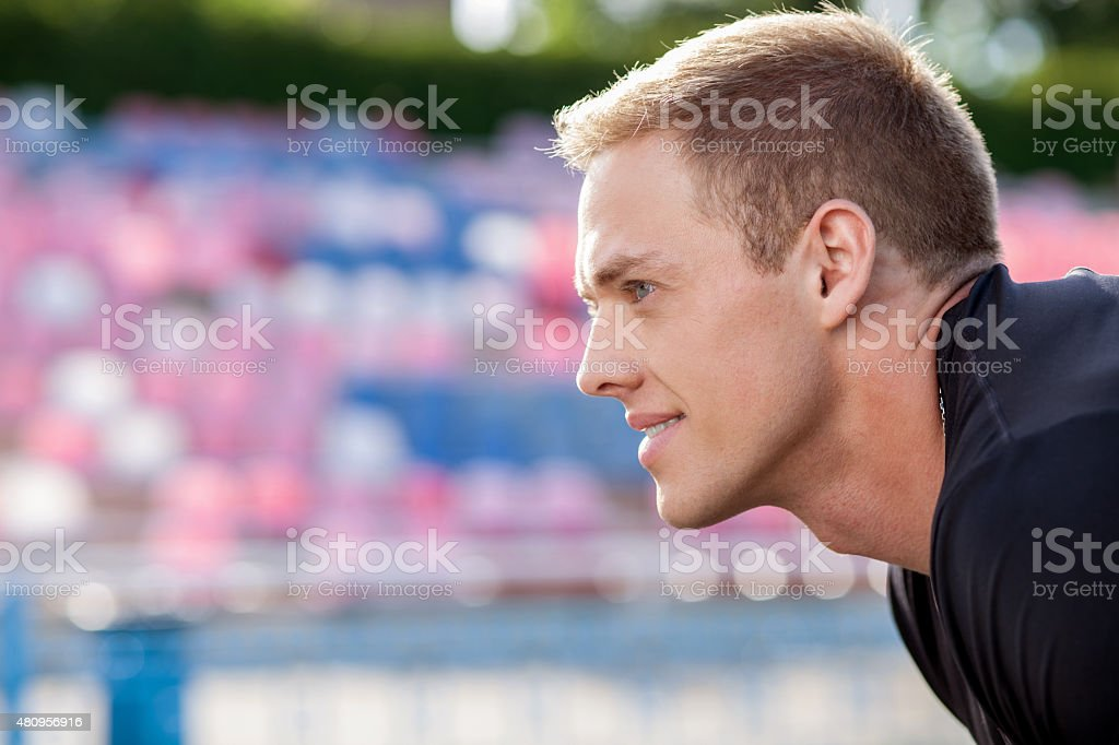 Handsome young sportsman takes breath after running stock photo