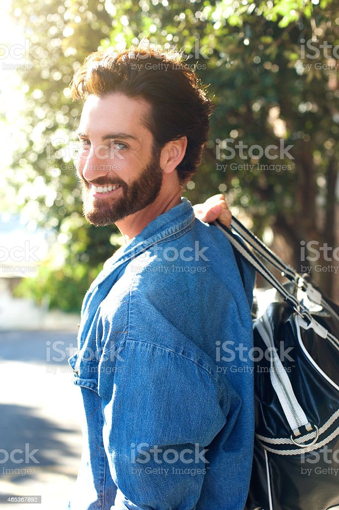 Handsome young traveling man smiling with bag stock photo