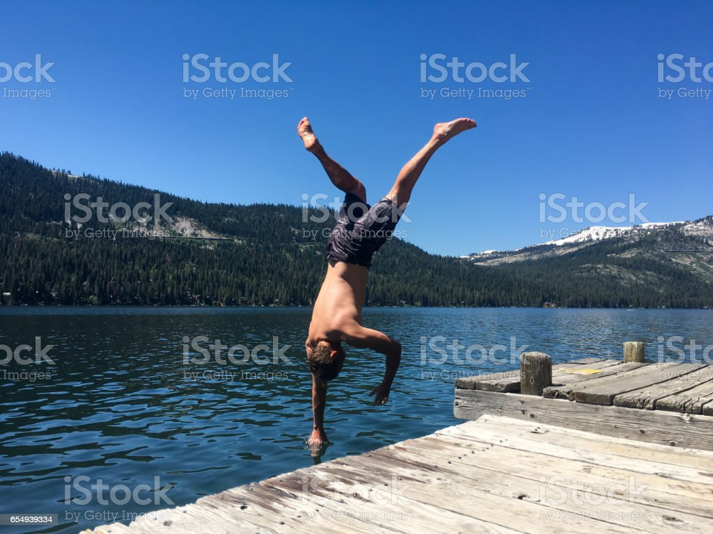Handstands into mountain lake stock photo