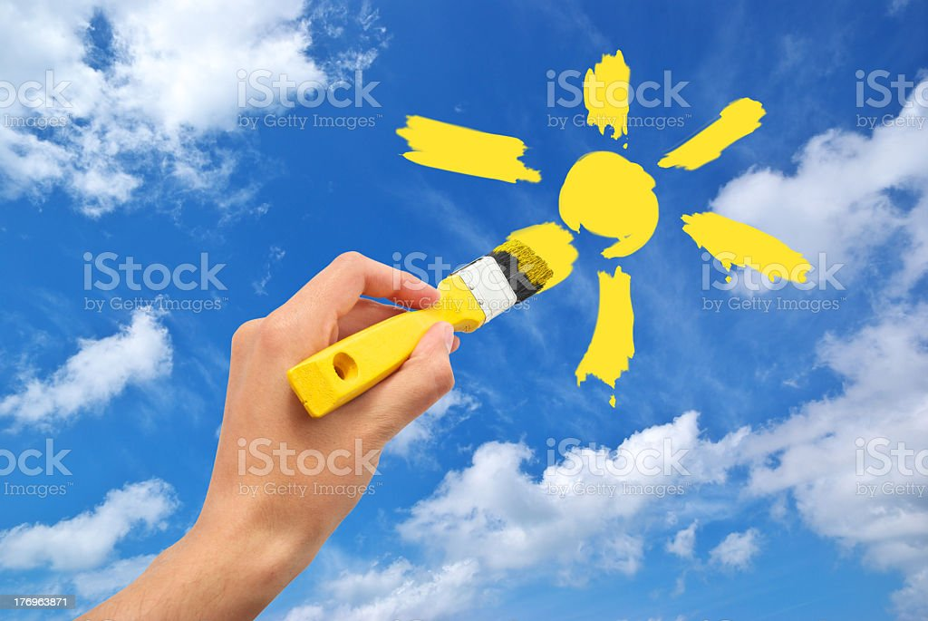 Handwriting a yellow sun in a cloudy sky stock photo