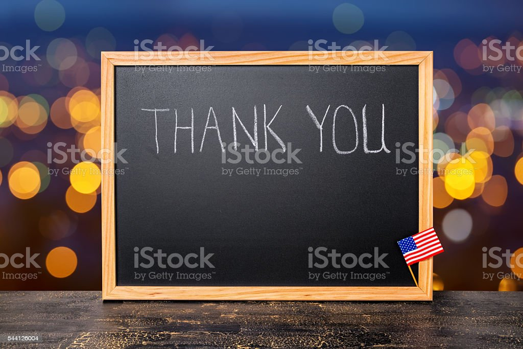 handwriting text thank you is written in chalkboard with flag stock photo