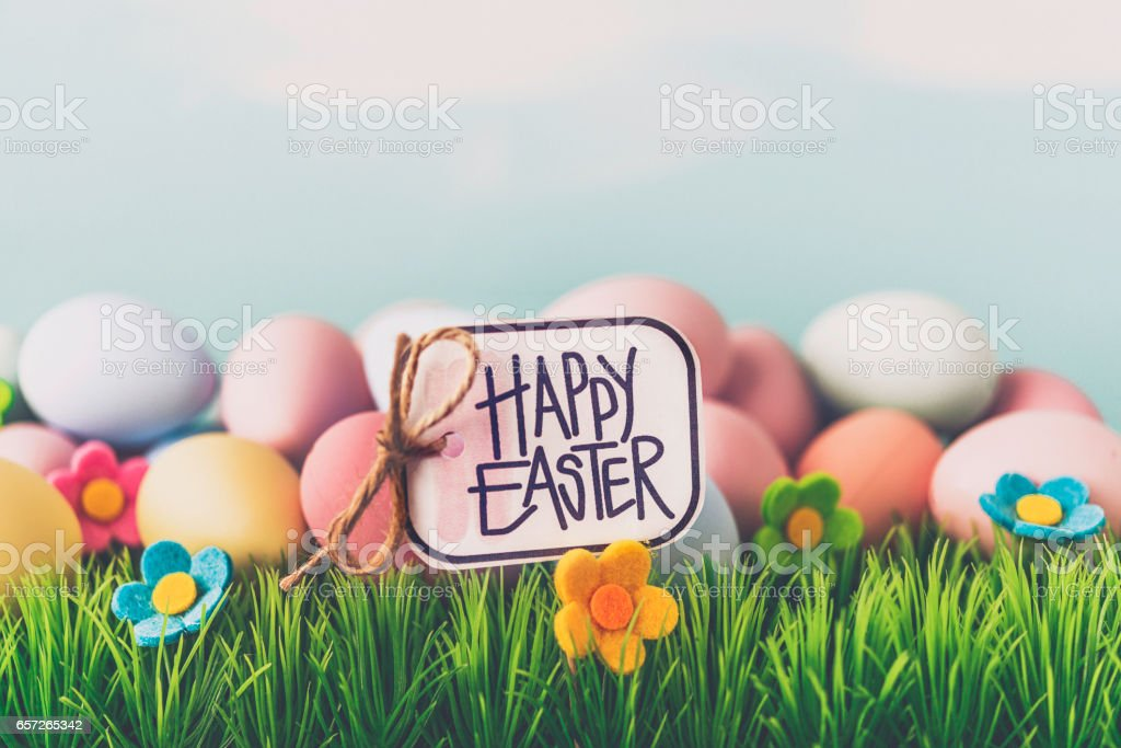 Handwritten Happy Easter message on sign in grass stock photo