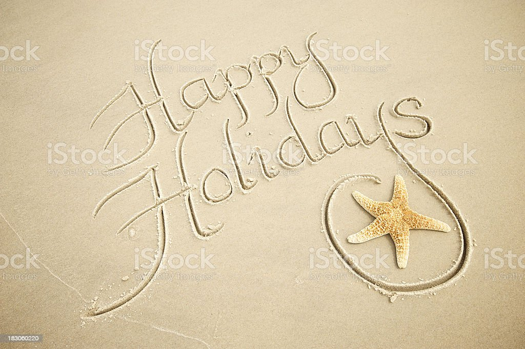 Handwritten Happy Holidays Greeting Message with Decorative Starfish in Sand royalty-free stock photo
