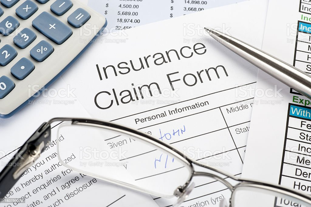 Handwritten Insurance Claim Form with pen and calculator stock photo