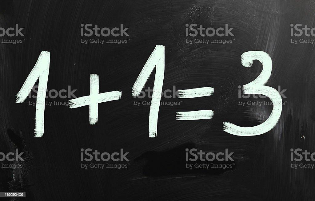 '1+1=3' handwritten with white chalk on a blackboard stock photo