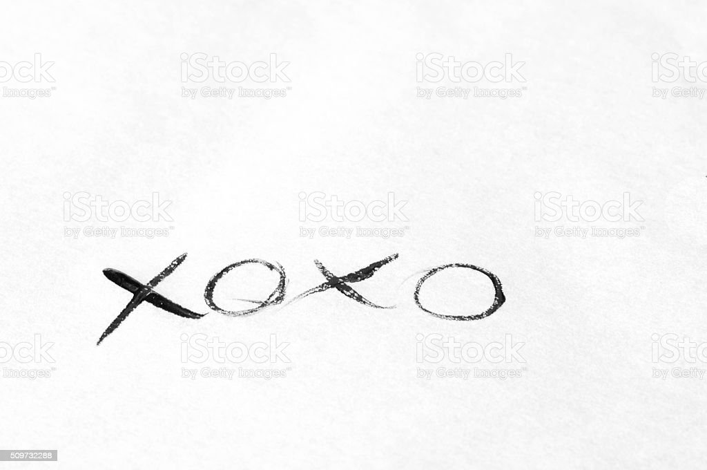 Handwritten 'xoxo' message with black ink on white paper stock photo