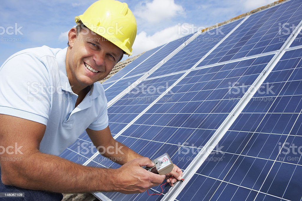 Handy man with yellow hat installing solar panels stock photo
