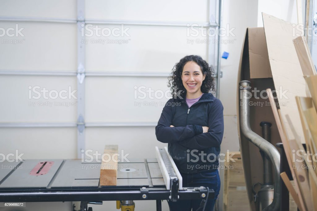 Young woman doing carpentry work in garage