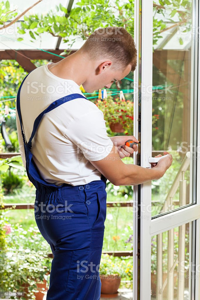 Handyman adjusting a window handle stock photo