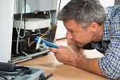 Handyman Checking Refrigerator With Flashlight At Home