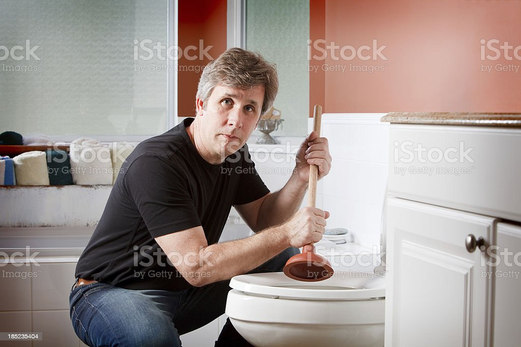 Handyman clearing a clogged toilet stock photo