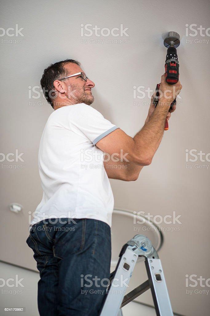 Handyman drilling a hole stock photo