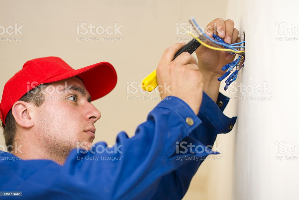 Handyman in a red hat checking wires royalty-free stock photo