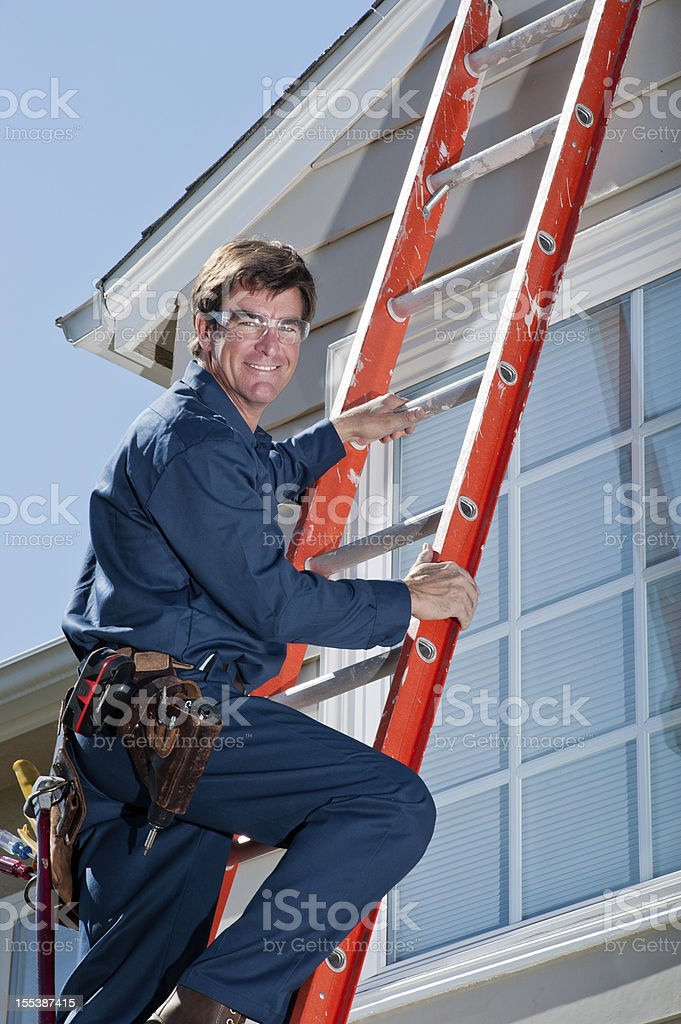 Handyman In Uniform Climbing Ladder royalty-free stock photo