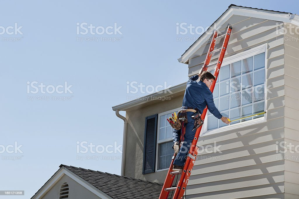 Handyman In Uniform Measuring Window stock photo