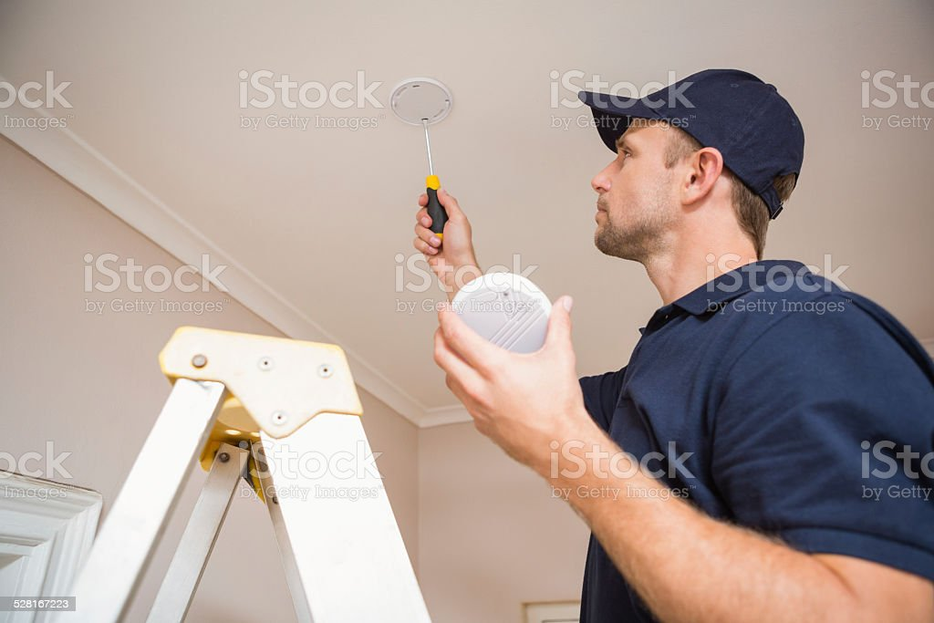 Handyman installing smoke detector stock photo