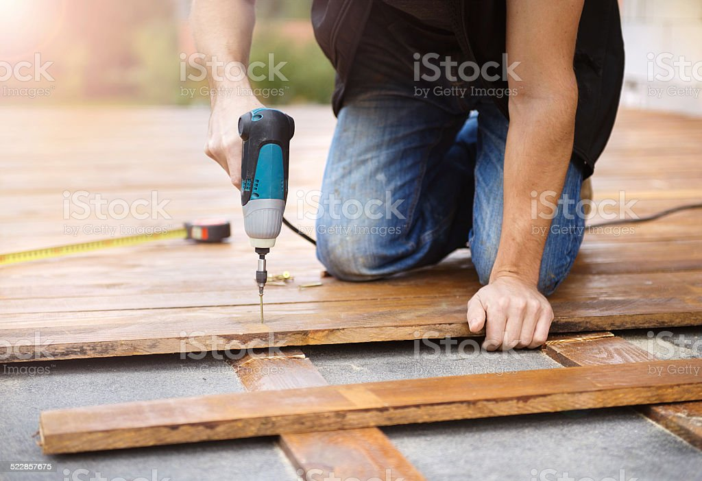 Handyman installing wooden flooring stock photo