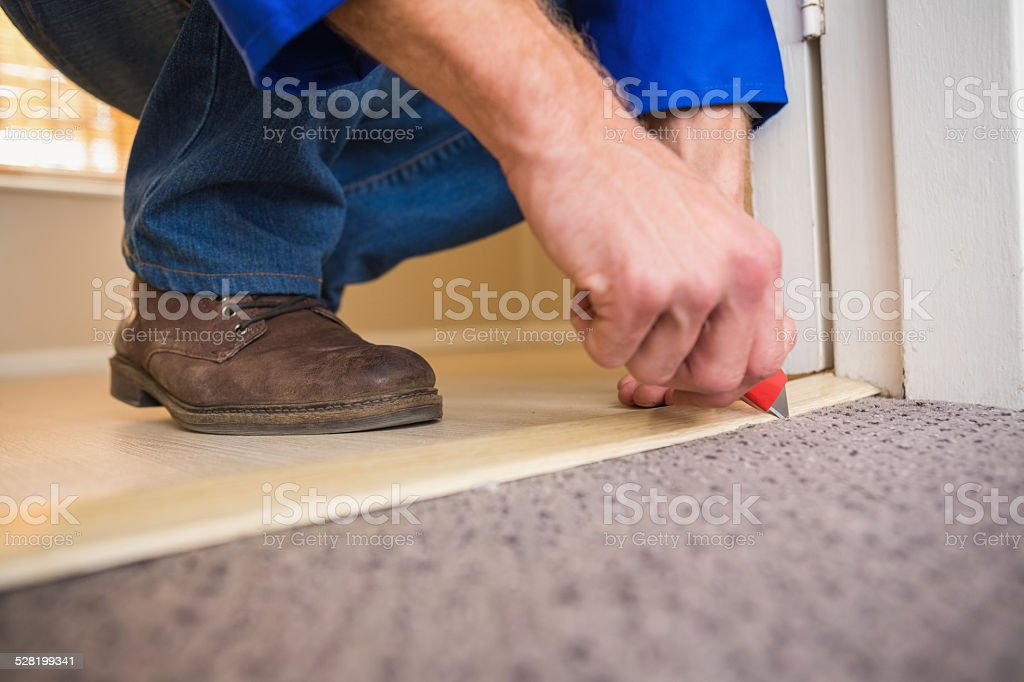 Handyman laying down a carpet stock photo