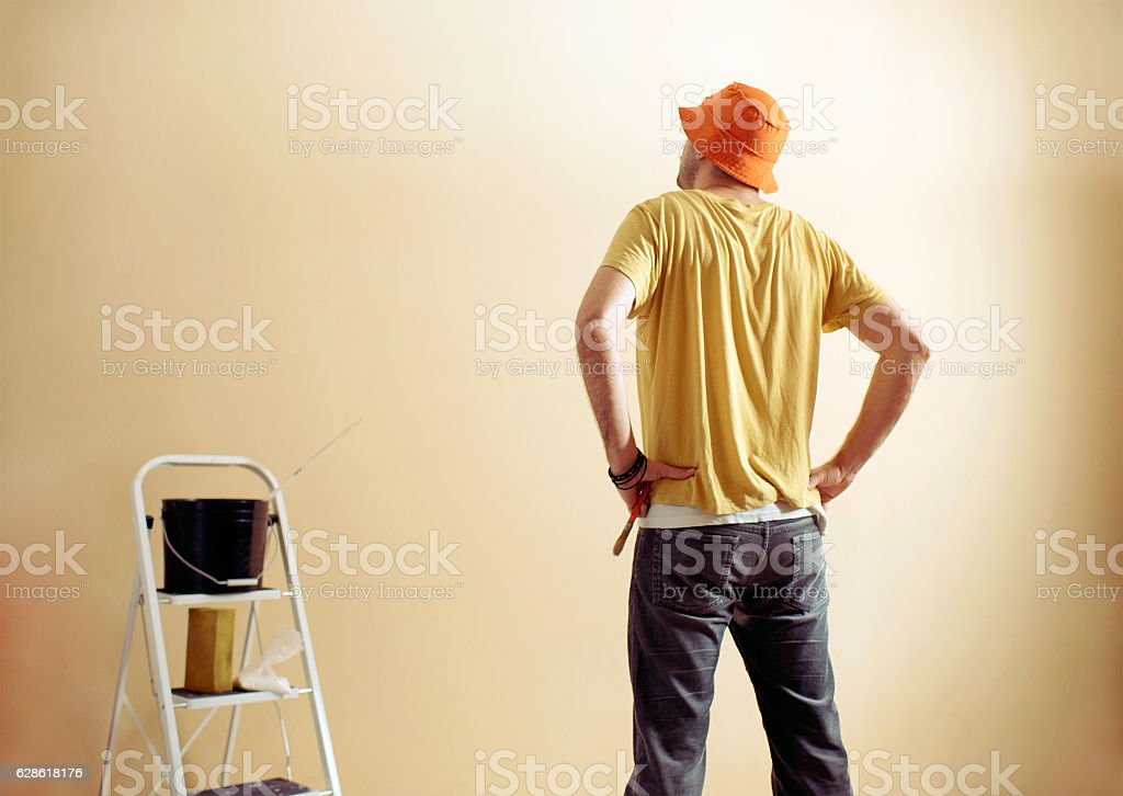 Handyman painting wall with background glue for a wallpaper stock photo