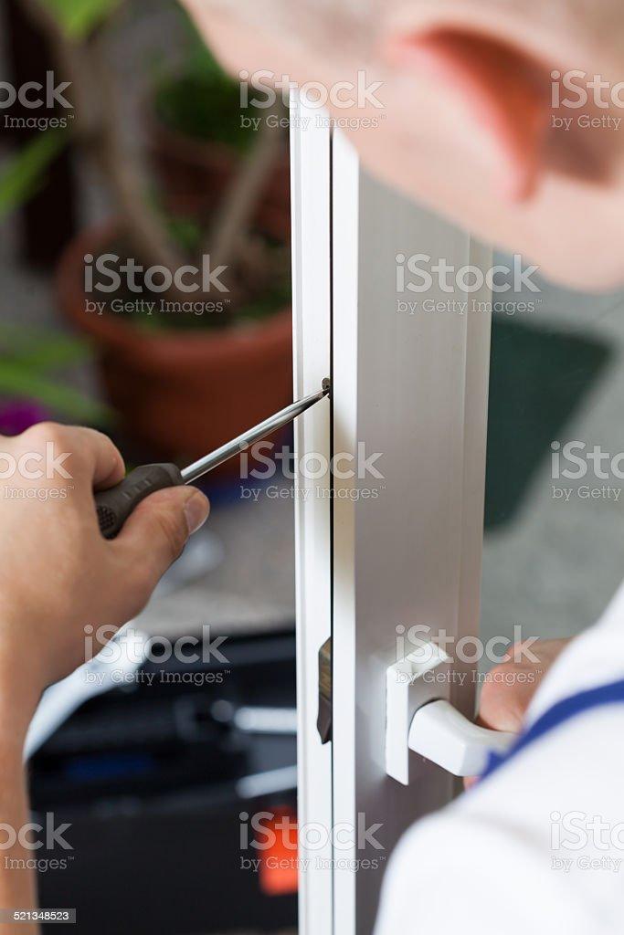 Handyman repairing window with screwdriver stock photo