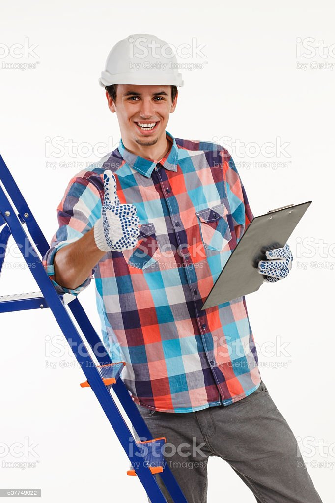 Handyman stood by ladder giving thumbs-up. stock photo