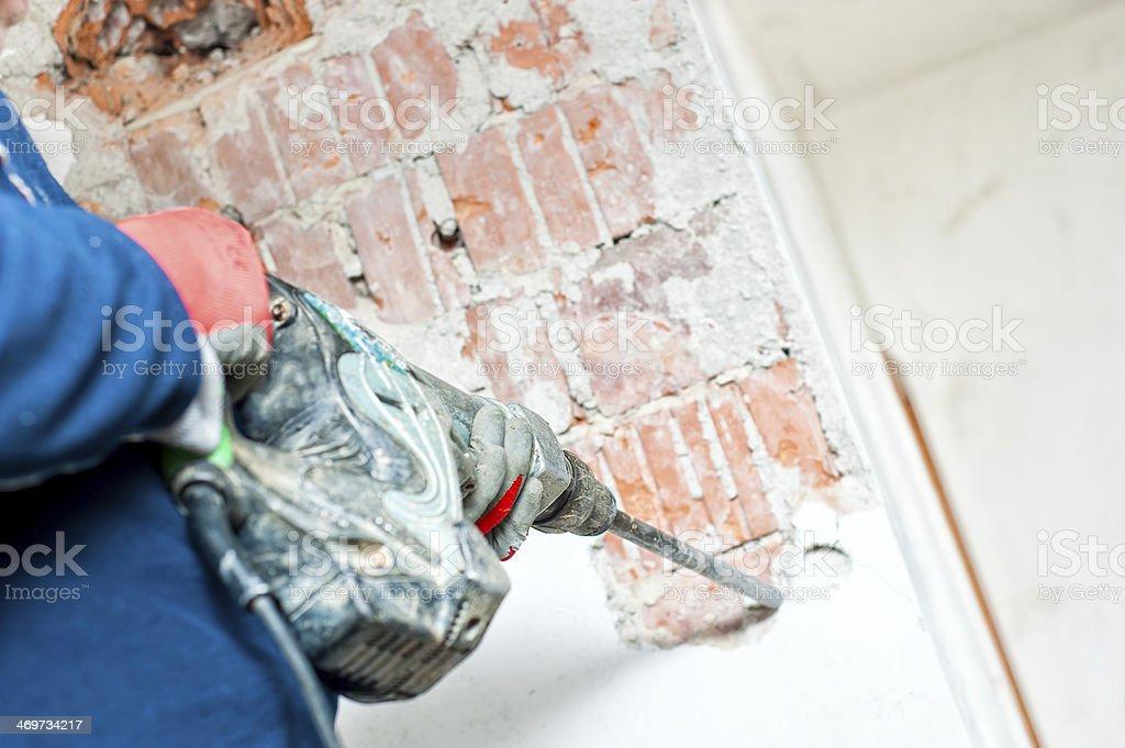 handyman using a jackhammer to distroy concrete interior walls stock photo