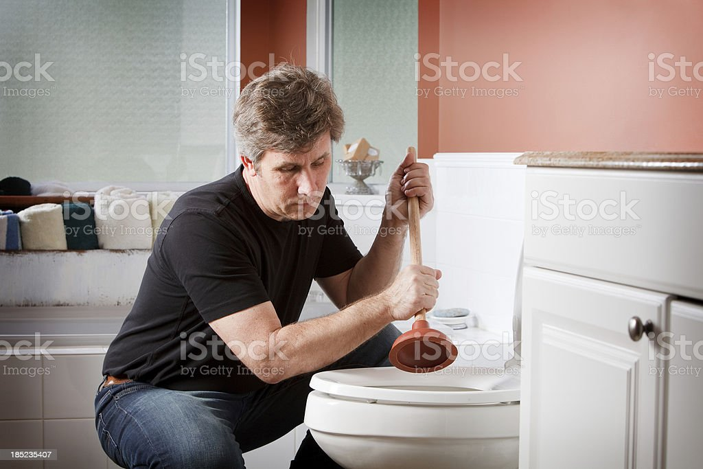 Handyman using plunger to clear a toilet stock photo