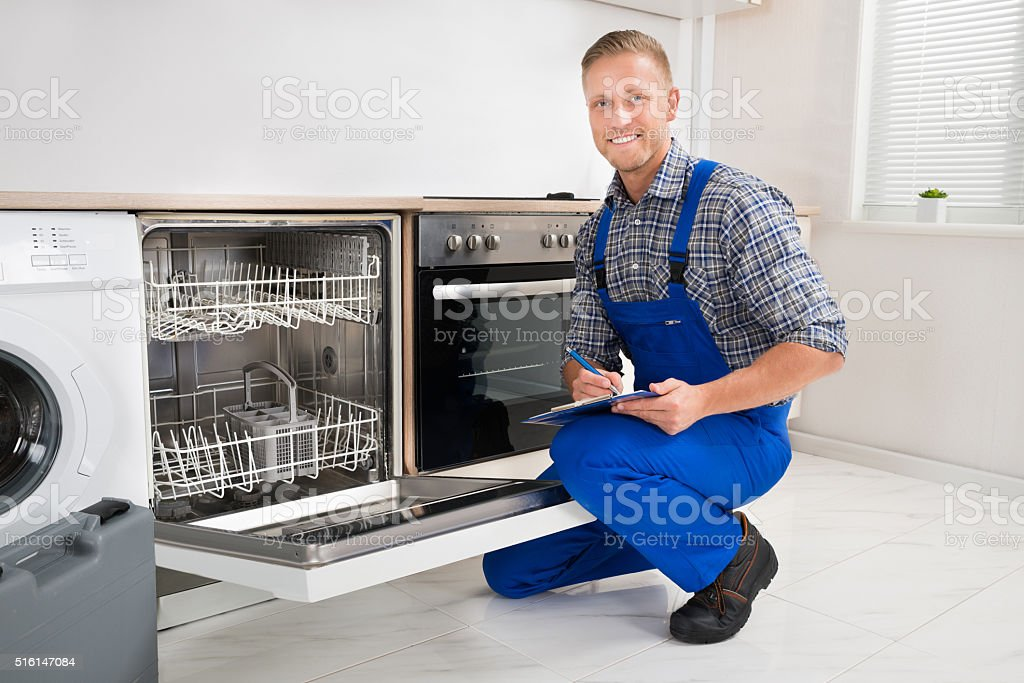 Handyman With Clipboard Looking At Dishwasher stock photo