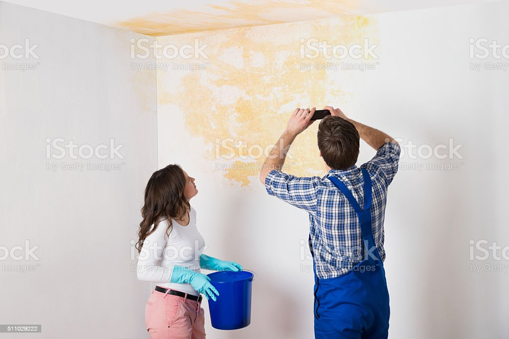 Handyman With Woman Photographing Ceiling At Home stock photo